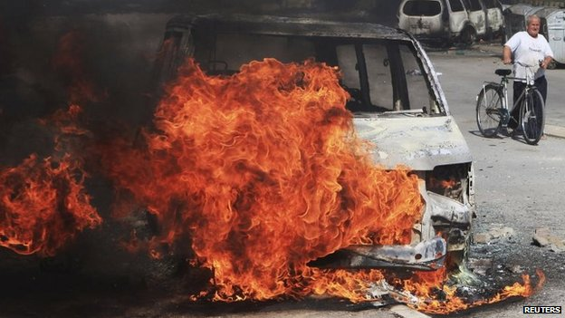 A man with a bicycle walks near a burning police vehicle set on fire by Kosovo Albanian demonstrators during a protest in the ethnically divided town of Mitrovica, Kosovo, 22 June 2014