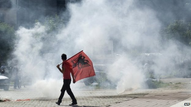 A Kosovo Albanian man, holding an Albanian flag, walks near tear gas fired by riot-police during clashes in Mitrovica, Kosovo, 22 June 2014