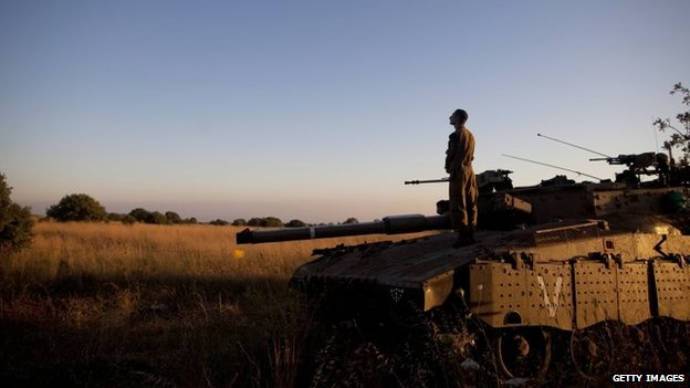 An Israeli soldier prays on a Merkava tank on the Israeli-Syrian border near Quneitra in the Golan Heights, 22 June 2014