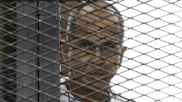 al-Jazeera journalist Peter Greste stands behind bars during his trial in a court in Cairo on 1 June 2014.