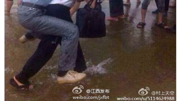 This man wearing leather shoes was carried on another man's back through ankle-deep water in Lantian Village