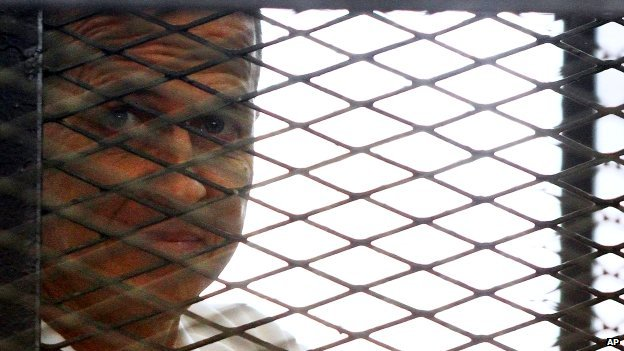 Al-Jazeera journalist Peter Greste looks out from a cage in a courtroom in Cairo, Egypt - Monday 23 June 2014