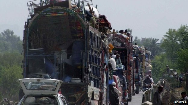 People fleeing the military offensive against the Pakistani militants in North Waziristan, travel atop a vehicle with their belongings while entering Bannu, located in Pakistan's Khyber-Pakhtunkhwa province, June 20, 2014.