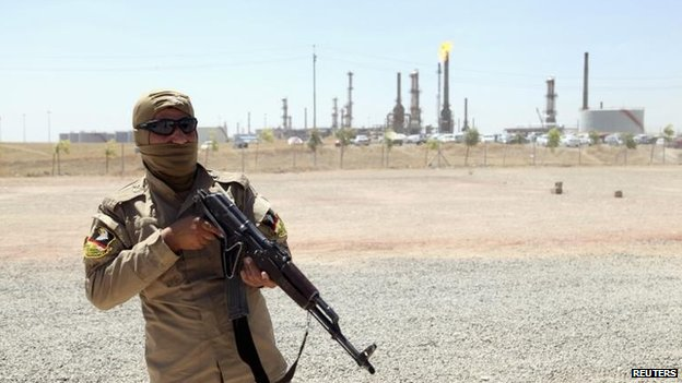Kurdish security forces guard an oil refinery near Mosul, 23 June
