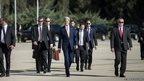 US Secretary of State John Kerry walks with his bodyguards towards a plane at Jordan's Queen Alia International Airport in Amman, Jordan
