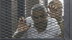 Mohamed Fahmy stands behind bars as he waits to listen the ruling at a court in Cairo on 23 June 2014.