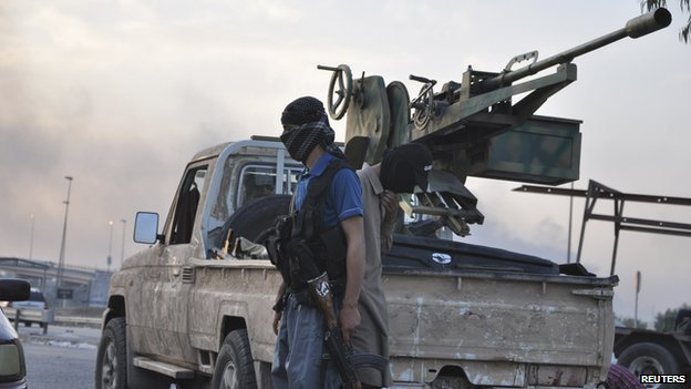 Isis fighter stands guard at an Iraqi checkpoint