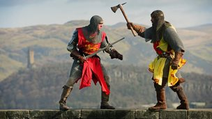 Two men dressed as medieval soldiers against the background of the Scottish hills