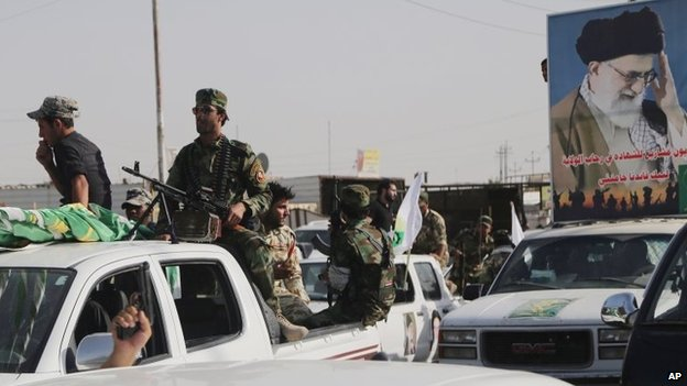 Armed Iraqi Shia militiamen parade through the city of Basra with a poster showing Iran's Supreme Leader, Ayatollah Ali Khamenei (14 June 2014)