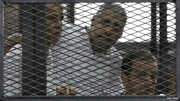 Peter Greste, Mohamed Fahmy and Baher Mohamed (L-R) listen to the ruling in court in Cairo - 23 June 2014