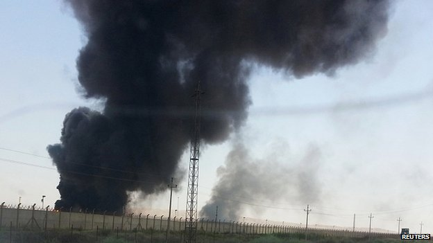 Smoke rises from a oil refinery in Baiji, north of Baghdad. 19 June 2014