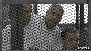Al-Jazeera journalists Peter Greste, Mohamed Fahmy and Baher Mohamed listen to proceedings from their cage in court
