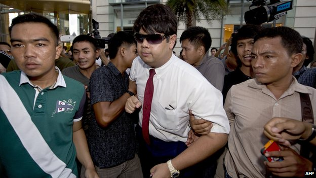 Thai policemen arrest an anti-coup protester (C) during a demonstration at a shopping mall in Bangkok on 22 June 2014.