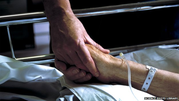 Two people holding hands. One is lying in a hospital bed with an intravenous drip.