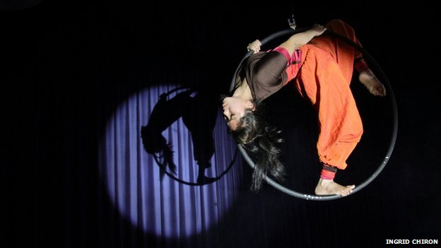 Circus performer upside down on ring