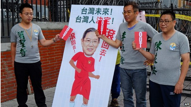 Supporters from the opposition Taiwan Solidarity Union display red cards next to an image of Zhang Zhijun, director of China's Taiwan Affairs Office, outside the parliament during a protest in Taipei on 24 June 2014.