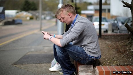 Two young men looking at their mobile phones