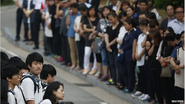 Students who survived the 16 April ferry disaster gather at the main gate as they make their way back to school in Ansan 25 June 2014.