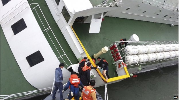 In this 16 April 2014 photo released by South Korea Coast Guard via Yonhap News Agency, South Korean coast guard officers rescue South Korean ferry Sewol Captain Lee Joon-seok, wearing a sweater and underwear, from the ferry in the water off the southern coast near Jindo, South Korea.