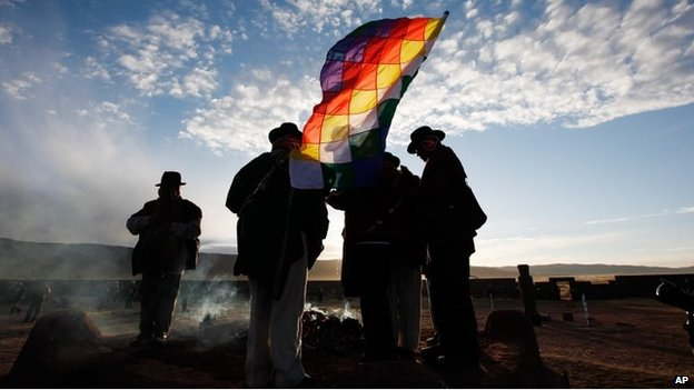 Aymara indigenous men with a Wiphala flag attend a new years ritual at the ruins of the ancient civilization of Tiwanaku located in the highlands in Tiwanaku, Bolivia, early Saturday, June 21, 2014