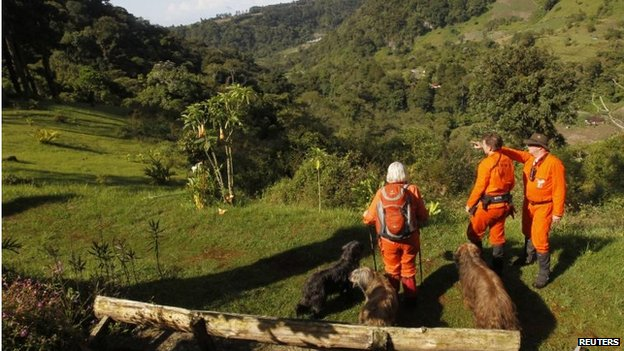 Sniffer dogs and members of independent Dutch rescue group Reddingshonden RHWW survey the landscape on a hiking trail during the second day of a search for two missing Dutch tourists in Boquete on 28 May, 2014.