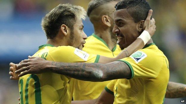 Brazil's Neymar celebrates with Luiz Gustavo and Dani Alves after scoring against Cameroon