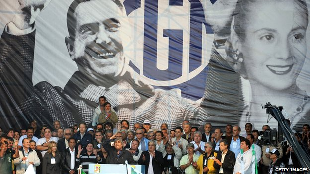 Union leader Hugo Moyano delivers a speech from the stage decorated with the images of former Argentine President Juan Domingo Peron and his wife Evita Peron to thousand of workers who attend to the celebration of the Labour Day in Buenos Aires on 30 April, 2009.
