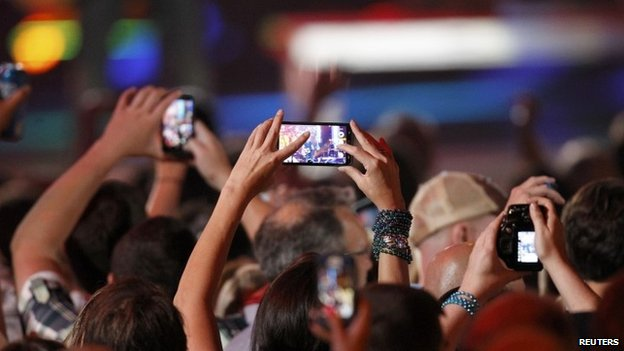 A fan uses a cell phone to record a performance during the 2014 CMT Music Awards in Nashville, Tennessee 4 June 2014