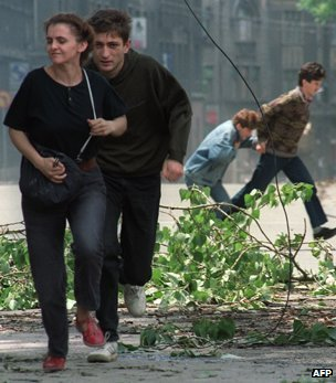 Sarajevo residents run through an intersection known for sniper activity after a shell fell in the center of the city on June 20, 1992.