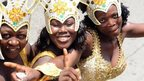 Women pose in their costumes in a procession during the yearly Lagos carnival on 9 April 2012