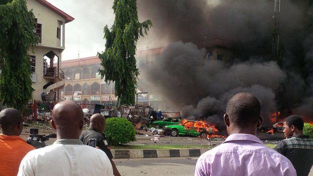 People watch as smoke fills the sky after an explosion at a shopping mall, on 25 June 2014, in Abuja, Nigeria.