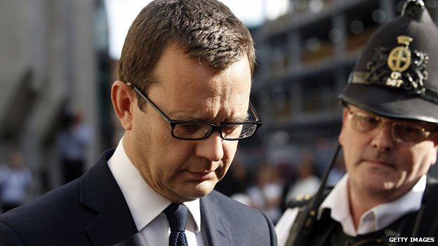 Andy Coulson leaves the Old Bailey, watched by a police officer