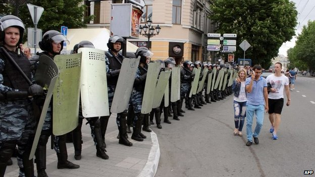 People walk past officers the Russian riot police force OMON blocking a street in the Crimean capital Simferopol