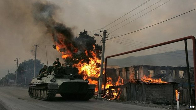 A Russian armoured troop-carrier moves with soldiers (troops) atop next to a house set on fire by South Ossetian militia