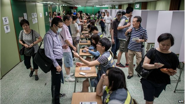 A volunteer hands a voter's ID card at a polling station in Hong Kong on 22 June 2014.