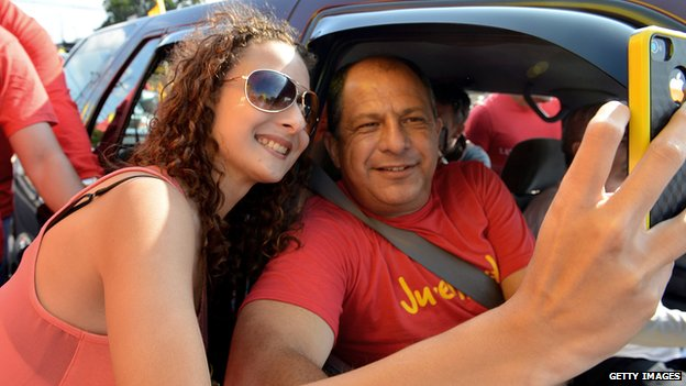 Luis Guillermo Solis takes a picture with a supporter along the streets of Coronado on 30 March, 2014