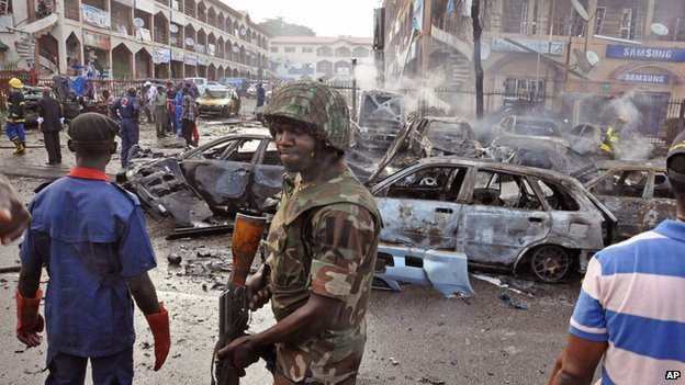A Nigerian soldier walks at the scene of an explosion in Abuja, Nigeria, on 25 June 2014