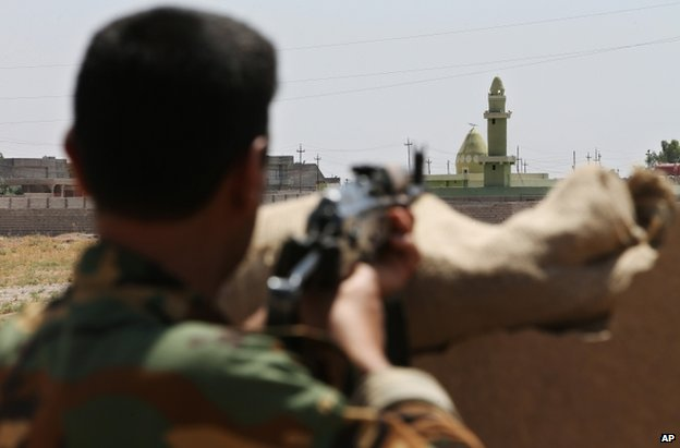 A Kurdish fighter watches an Isis position in Tuz Khormato, Iraq, 25 June