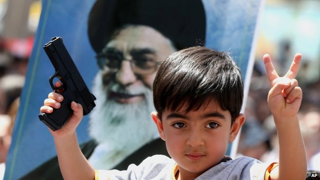 An Iraqi boy living in Iran holds a toy gun and flashes a victory sign in front of a poster of the Iranian Supreme leader Ayatollah Ali Khamenei