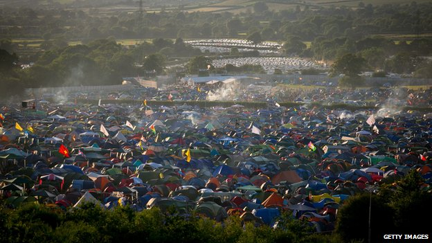 Smoke rises from festival revellers tents pitched at Worthy Farm in Pilton on the first day of the 2014 Glastonbury Festival on June 25, 2014