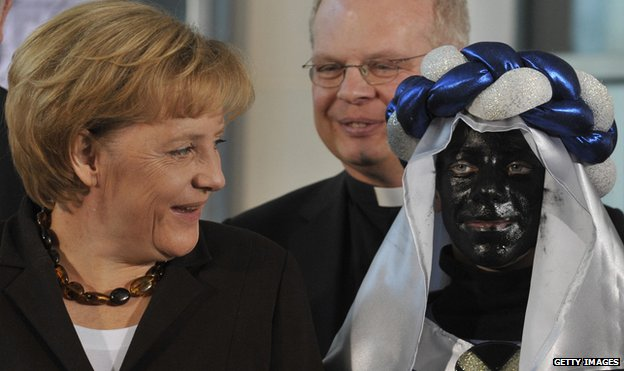 Angela Merkel and a child with a blacked up face on the Three Kings Day