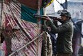 A policeman aims his pellet gun at Kashmiri protesters during a strike in Srinagar, the summer capital of Indian Kashmir, January 31 2014.