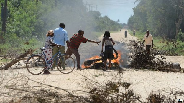 Locals block the road with a barricade as they protest the rising insecurity following the killings in Mpeketoni, 17 June 2014