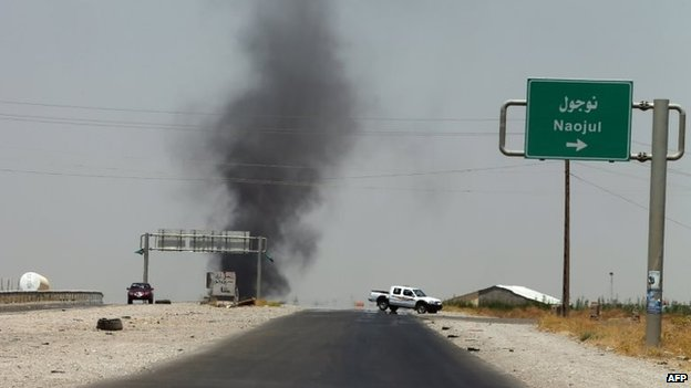 Smoke billows from an area controlled by the Islamic State of Iraq and the Levant (Isis) between the Iraqi towns of Naojul and Tuz Khurmatu