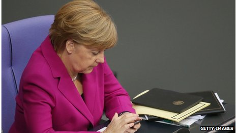 German Chancellor Angela Merkel types on a smartphone