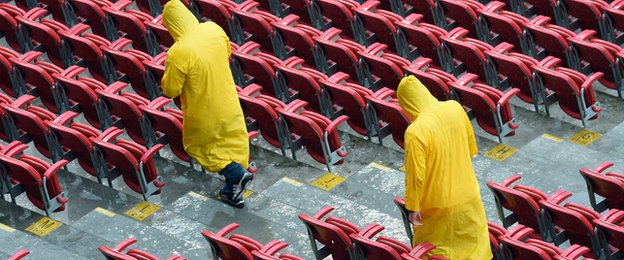 Stewards attempt to clear water from the stand