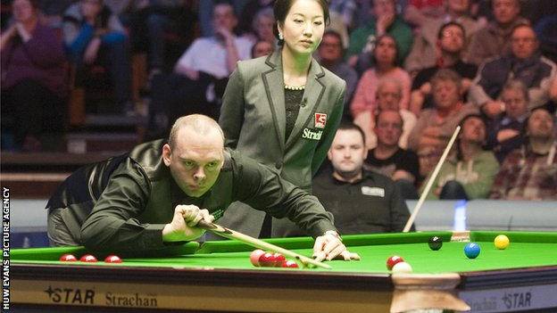 Stuart Bingham pots as match referee Zhu Ying watches
