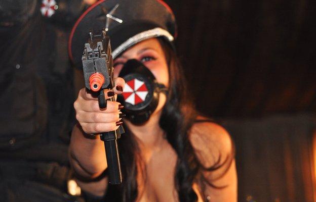 Cosplayer points gun