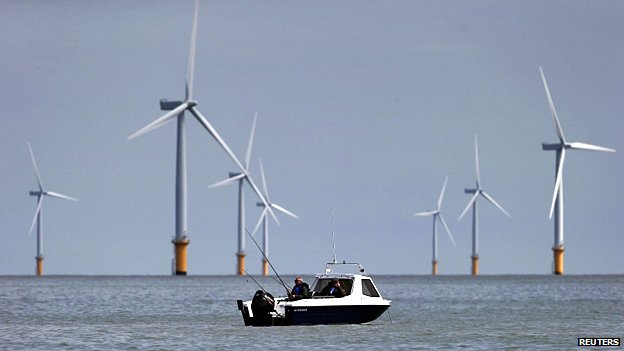 Two fishermen sit in their boat at the Gunfleet Sands Offshore Wind Farm near Clacton-on-Sea, Essex