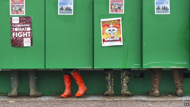 Wellingtons visible beneath the long-drop toilet doors at Glastonbury
